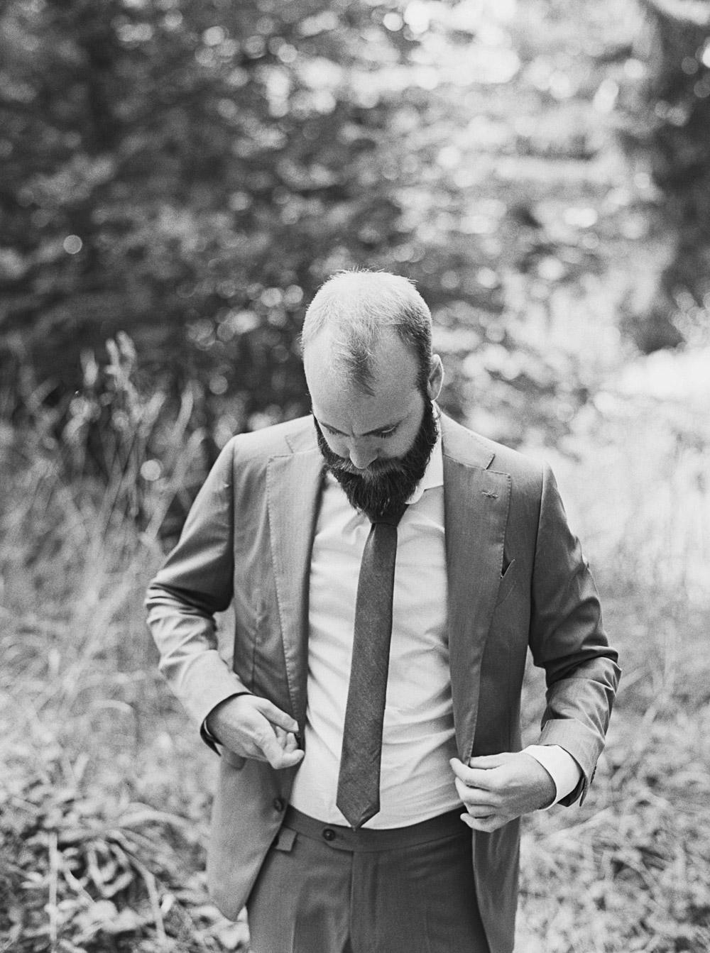 Seattle wedding photographer captures groom buttoning jacket at Wellspring Spa Wedding