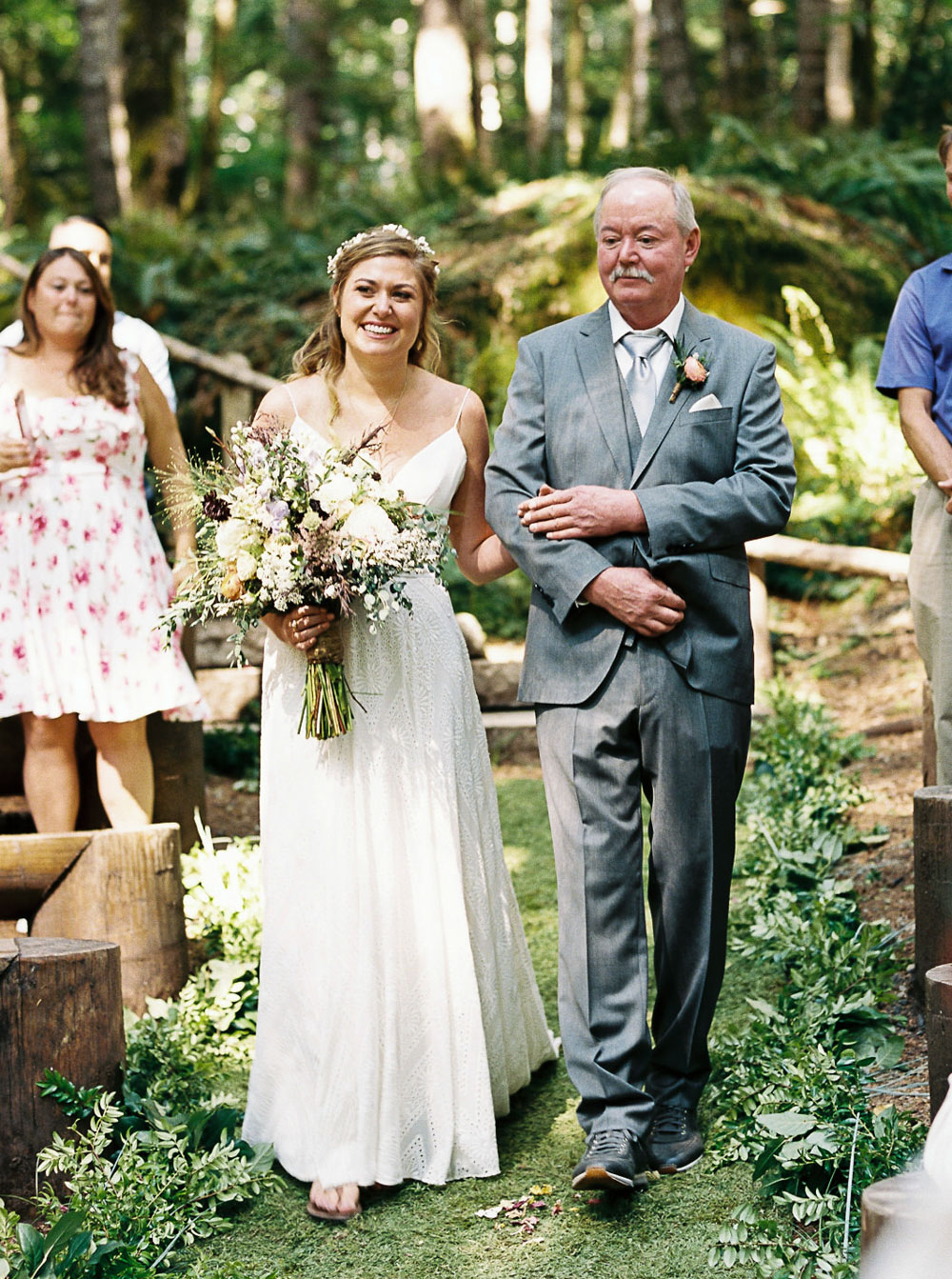 Bride and father walk down aisle during outdoor Washington wedding near Seattle at Wellspring Spa