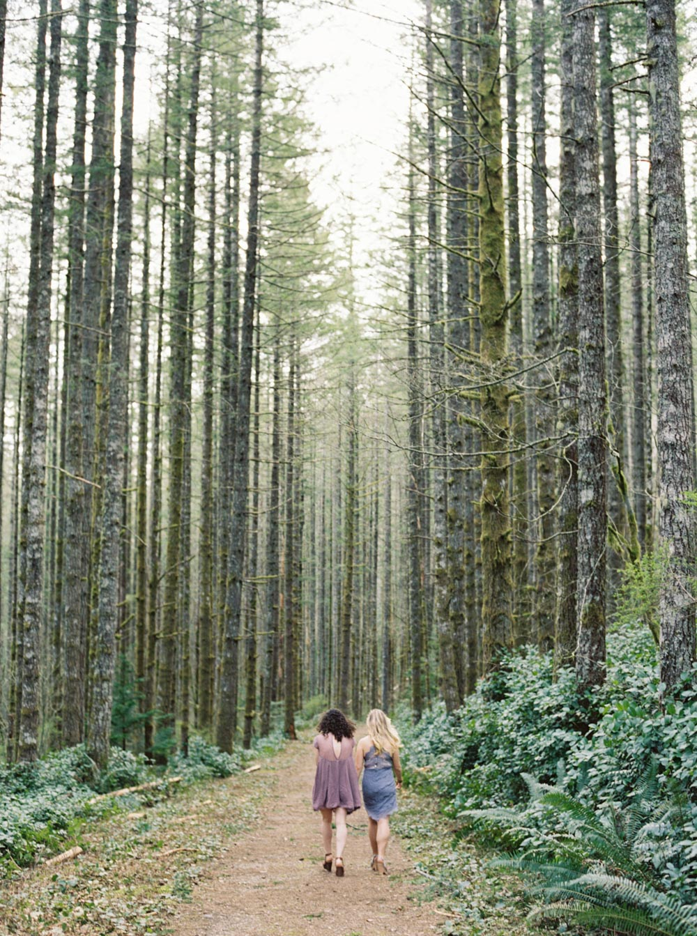 Couple walks through woods at Rattlesnake Ridge during their Seattle Engagement Photography Session by Anna Peters