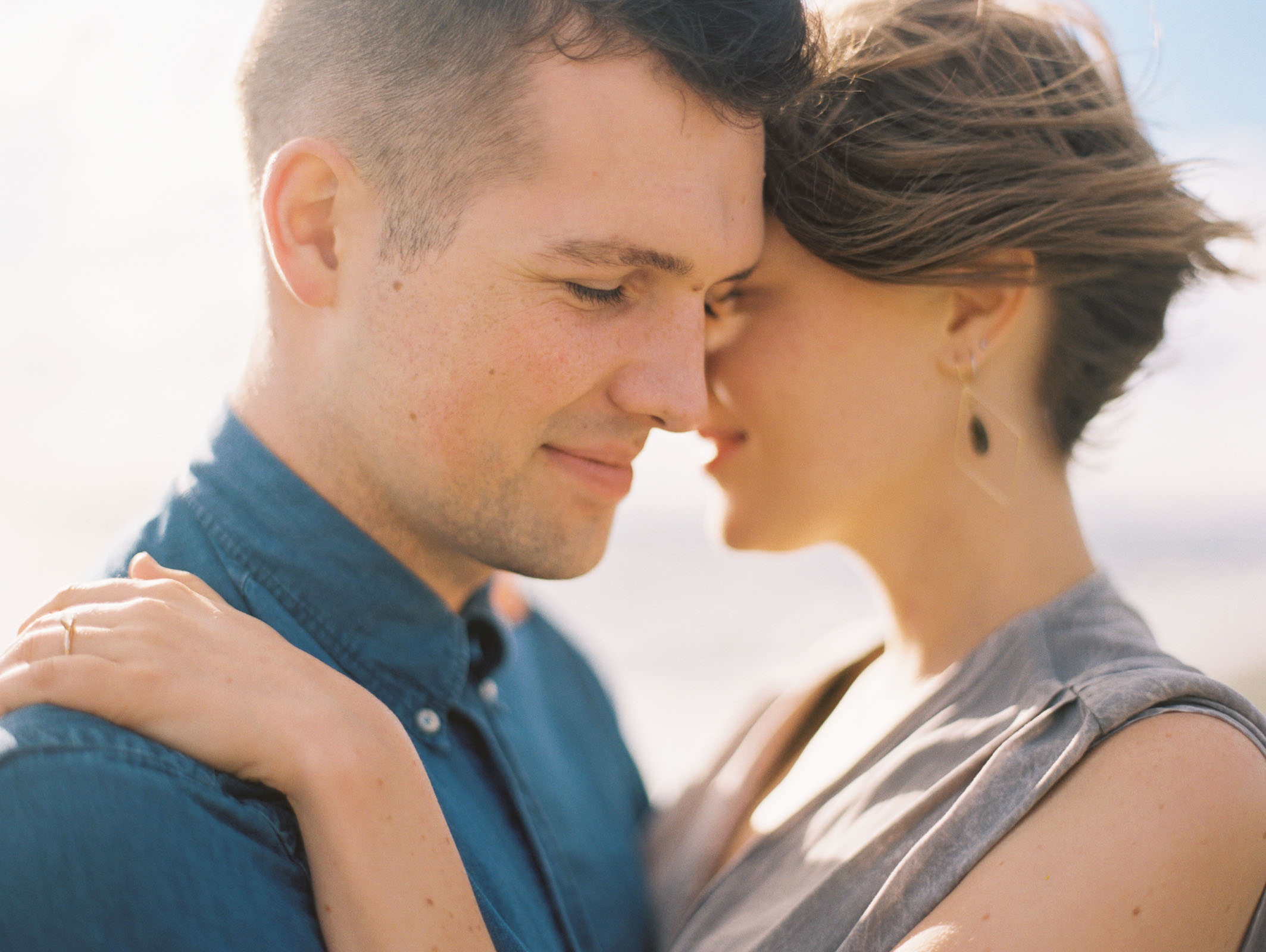 Embrace on the beach at Discovery Park captured by Seattle Engagement Photographer Anna Peters