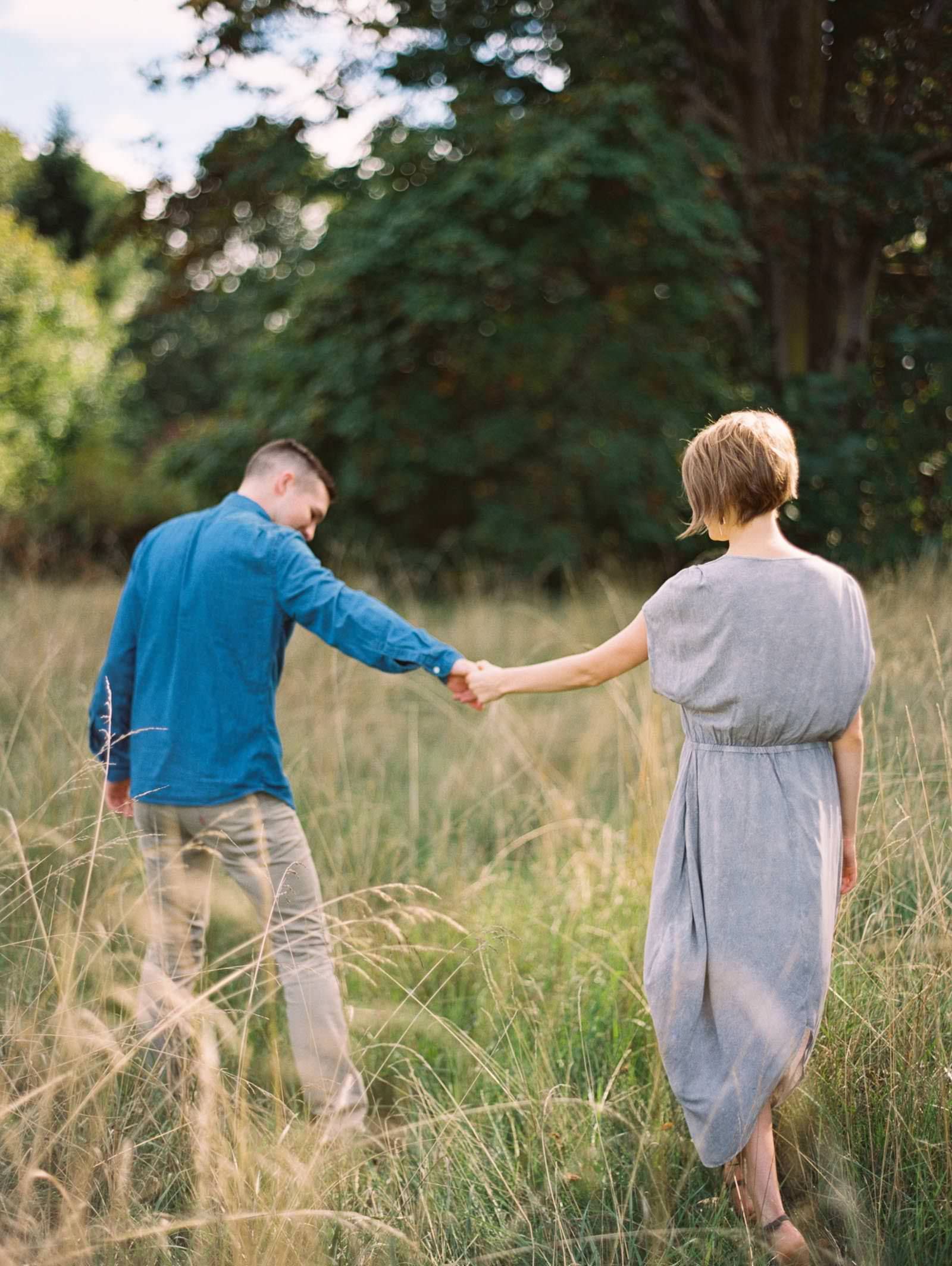 Walking through Discovery Park's fields captured by top Seattle Engagement Photographer Anna Peters
