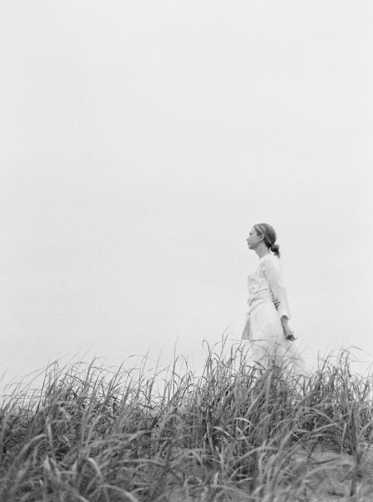 Portrait of woman in white dress near sand dunes